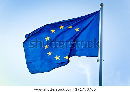 European Union flag in front of blue sky - EU flag close-up shoot on wind - stock photo