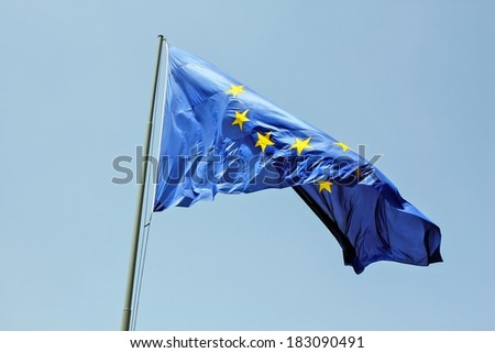 European Union flag in front of blue sky - EU flag  symbol of united Europe shoot on wind - stock photo