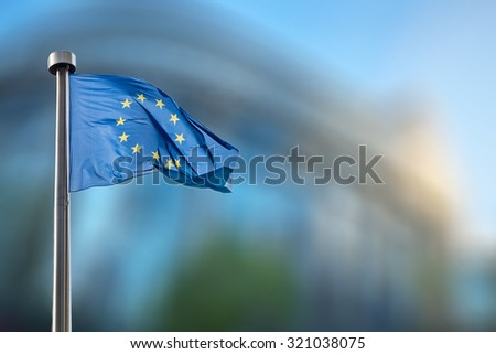 European Union flag in front of the blurred European Parliament in Brussels, Belgium