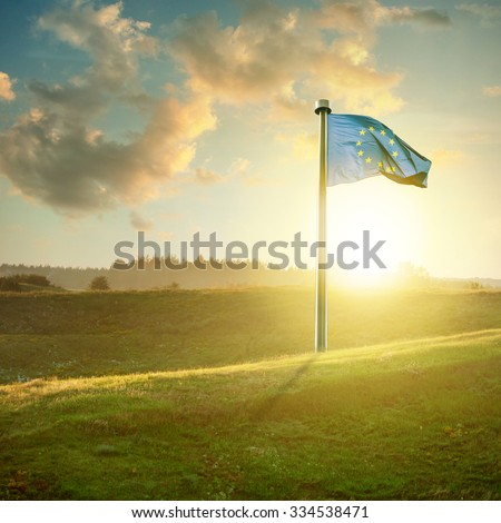 european union flag on sunset landscape with green field and beautiful clouds - stock photo