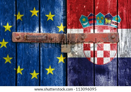 European Union flag with the Croatian flag on the background of old locked doors - stock photo