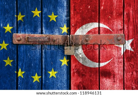 European Union flag with the Turkish flag on the background of old locked doors - stock photo