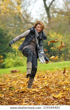 European woman kicking yellow leaves in autumn. - stock photo