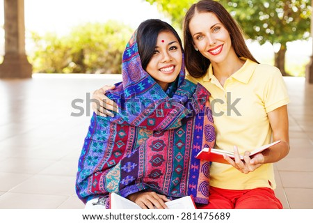 European woman volunteering in Nepal, teaching a poor asian woman to speak English language - stock photo