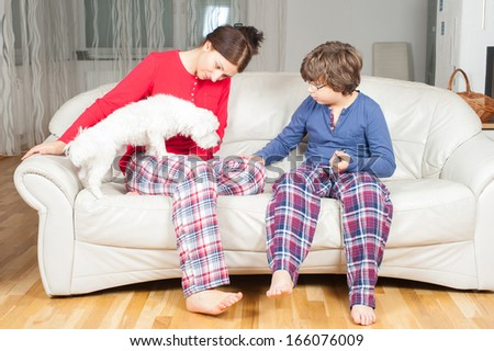European woman with son in pajamas on the couch, next to a small white dog - stock photo