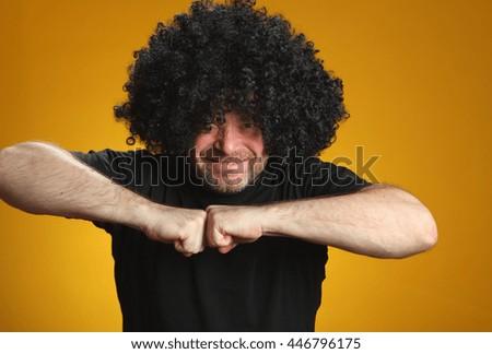 European young man in a dark wig on a yellow background. bright yemotsiyi. studio photo - stock photo