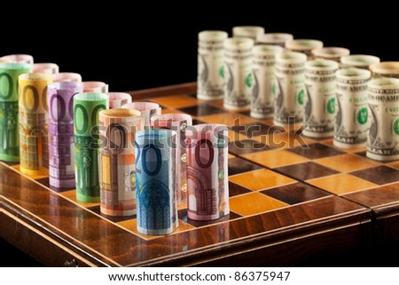 Euros and dollars on chess board - closeup - stock photo