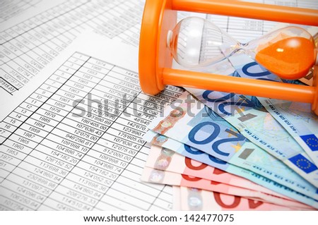 Euros and sand-glass on documents. - stock photo