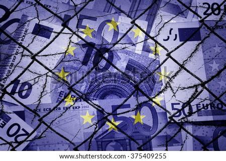 Euros, fence, EU flag and cracks - Finance/Business concept - stock photo