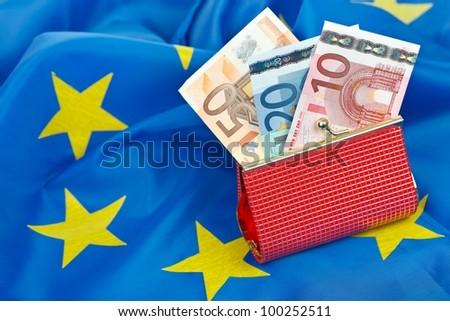Euros in wallet on the flag of the European Union - stock photo