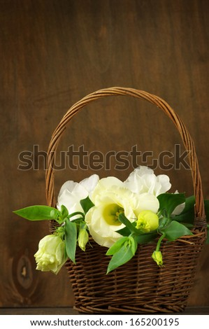Eustoma flowers in wicker basket on wooden background.