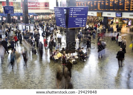 Euston station in the rush hour, London UK. All faces blurred beyond recognition and trademarks/logos removed. - stock photo