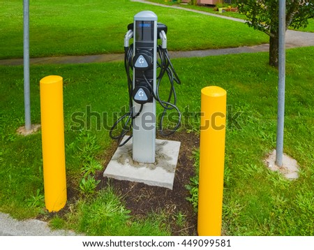 EV charger on green grass lawn. EV - electric vehicle charging station. Electric car charging point with yellow pillars around. - stock photo