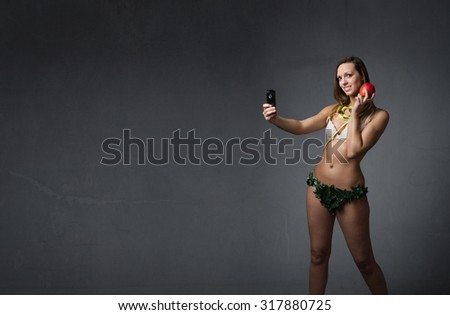 eve taking selfie with apple, dark background - stock photo