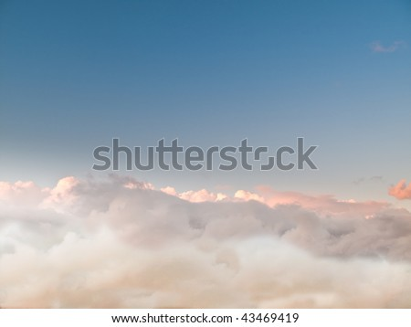 Evening above the clouds, an ocean of soft fluffy white stratocumulus clouds, moving with the wind. Rich blue sky. - stock photo