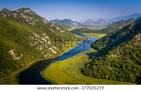 Evening aerial photo of the river Crnojevica between the green hills and mountains. Fairy tale lands of Montenegro. - stock photo