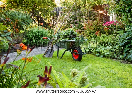 Evening after work in summer garden with wheelbarrow, shovel and rake - horizontal - stock photo
