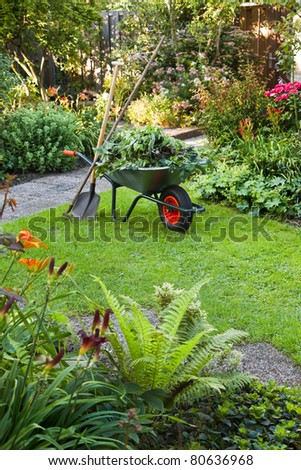 Evening after work in summer garden with wheelbarrow, shovel and rake - vertical - stock photo