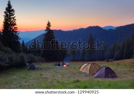 Evening by the fire in the mountains. Camping in tents in the mountains. - stock photo