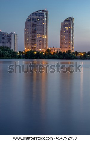 Evening city buildings reflected in river water