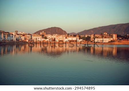 Evening cityscape above holy lake with mountains around, Pushkar city, popular touristic town in Ajmer district of India - stock photo