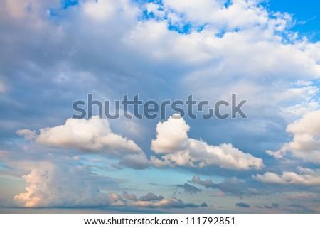 evening cumulus clouds in blue summer sky - stock photo