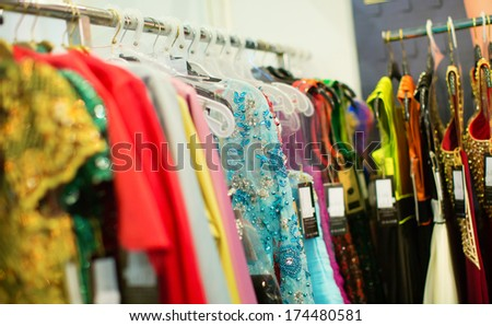Evening dresses hang on a shelf in a store