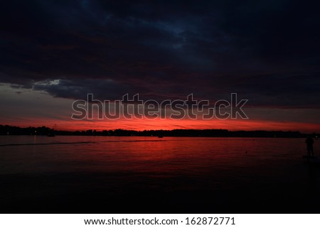 Evening fiery red sunset colors and clouds over Lake James in Angola, Indiana USA. - stock photo