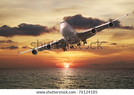 Evening flight. Jet plane over the sea at sunset.