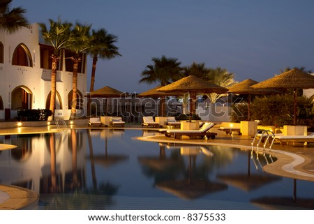 evening illumination in tropical hotel. swimming pool and sunshades
