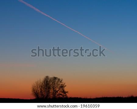 evening landscape, airplane on sunset sky - stock photo