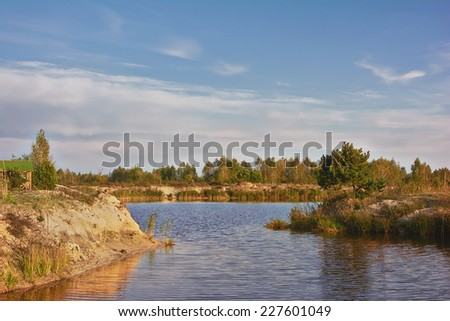 Evening landscape - pond, forest on coast and blue sky with clouds