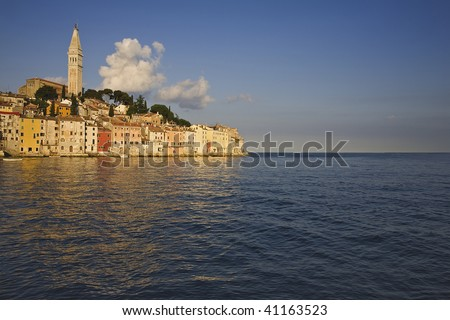 Evening light catching the pastel colored buildings of Rovinj which sits on the western coast of Istria in Croatia. - stock photo