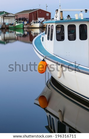 Evening light on lobster boats tied up at the wharf in rural Prince Edward Island, Canada. - stock photo