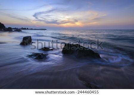 Evening light sunset sea waves splashing rocks.  - stock photo