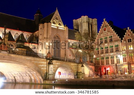 Evening lights illuminate stone arches of St Michael's bridge and nearby church at night, Ghent, Belgium