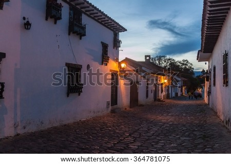 Evening moody view of a cobbled street in colonial town Villa de Leyva, Colombia. - stock photo