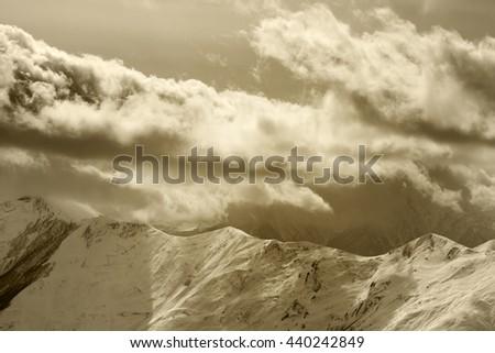 Evening mountains and cloudy sky. Caucasus Mountains. Georgia, region Gudauri. Sepia toned. - stock photo