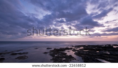 Evening on a rocky coast  with a dramatic moody sky at Paphos area in Cyprus. - stock photo