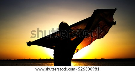 Evening on seashore. Silhouette of girl with handkerchief in his hands at sunset.