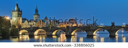 Evening panorama of the Charles Bridge in Prague, Czech Republic, with Old Town Bridge Tower, Old Town Water Tower and dome of the National Theatre - stock photo