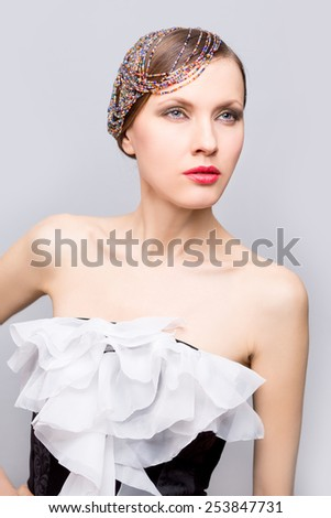 Evening party woman. Fashion photo of beautiful woman with creative hairdo with bead strands and evening dress - stock photo