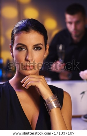Evening portrait of attractive young woman in black dress. Man at background. - stock photo