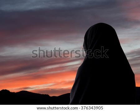 Evening prayers? Muslim woman in chador against sunset sky. - stock photo