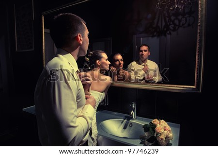 Evening preparing of couple  in the restroom for going out - stock photo