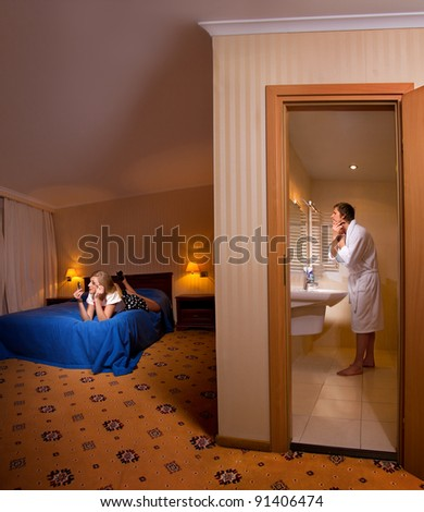 Evening preparing of family for going out. Man shaving in the bathroom and his wife making up on bed - stock photo
