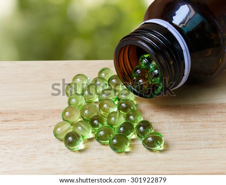 Evening primrose oil capsule on wood with abstract bokeh background of nature - stock photo