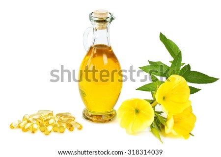 Evening primroses with gelatine capsules and oil bottle on white background - stock photo