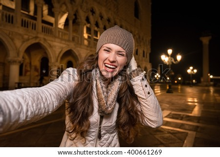 Evening promenade in Venice take you into another world. Happy young woman tourist taking selfie on St. Mark's Square near Dogi Palace in the evening. - stock photo
