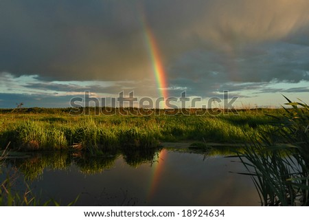Evening rainbow above a small reservoir among a deserted field
